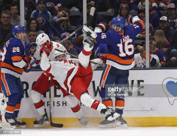 Andrew Ladd of the New York Islanders checks Jake Gardiner of the Carolina Hurricanes during the third period at NYCB Live's Nassau Coliseum on March...