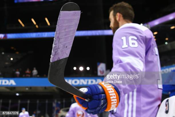 Andrew Ladd of the New York Islanders dons special stick tape in honor of Hockey Fights Cancer before a game against the Colorado Avalanche at...