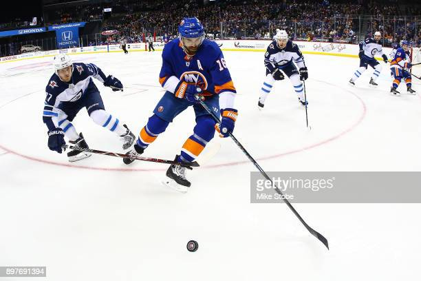 Andrew Ladd of the New York Islanders pursues the puck against Nikolaj Ehlers of the Winnipeg Jets at Barclays Center on December 23 2017 in New York...