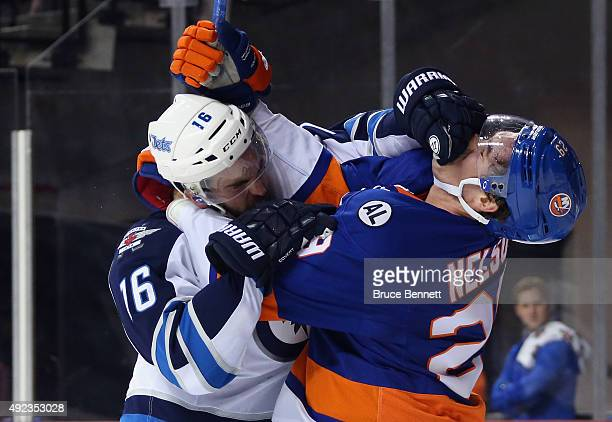 Andrew Ladd of the Winnipeg Jets and Brock Nelson of the New York Islanders battle during the second period at the Barclays Center on October 12 2015...