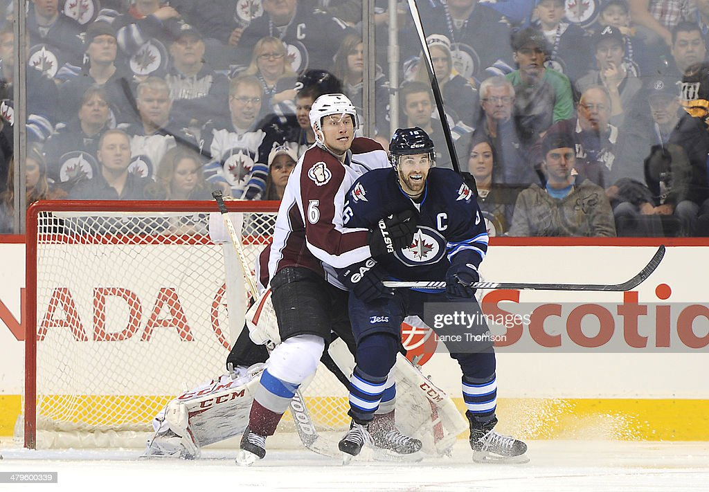 Andrew Ladd #16 of the Winnipeg Jets and Erik Johnson #6 of the Colorado Avalanche battle for position in front of the net as they keep an eye on the play during third-period action at the MTS Centre on March 19, 2014 in Winnipeg, Manitoba, Canada.