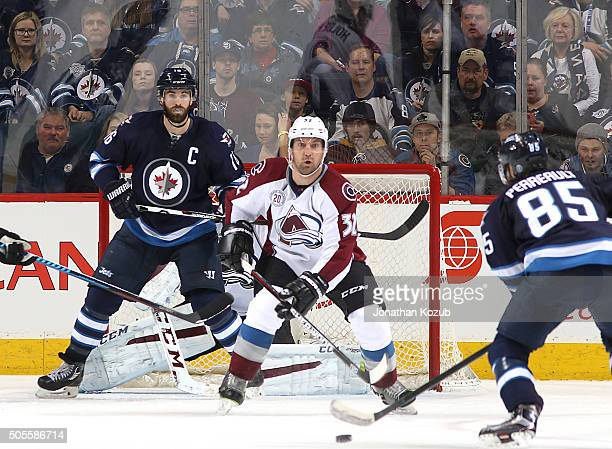 Andrew Ladd of the Winnipeg Jets and Francois Beauchemin of the Colorado Avalanche keep an eye on the point as Mathieu Perreault gets set to shoot...