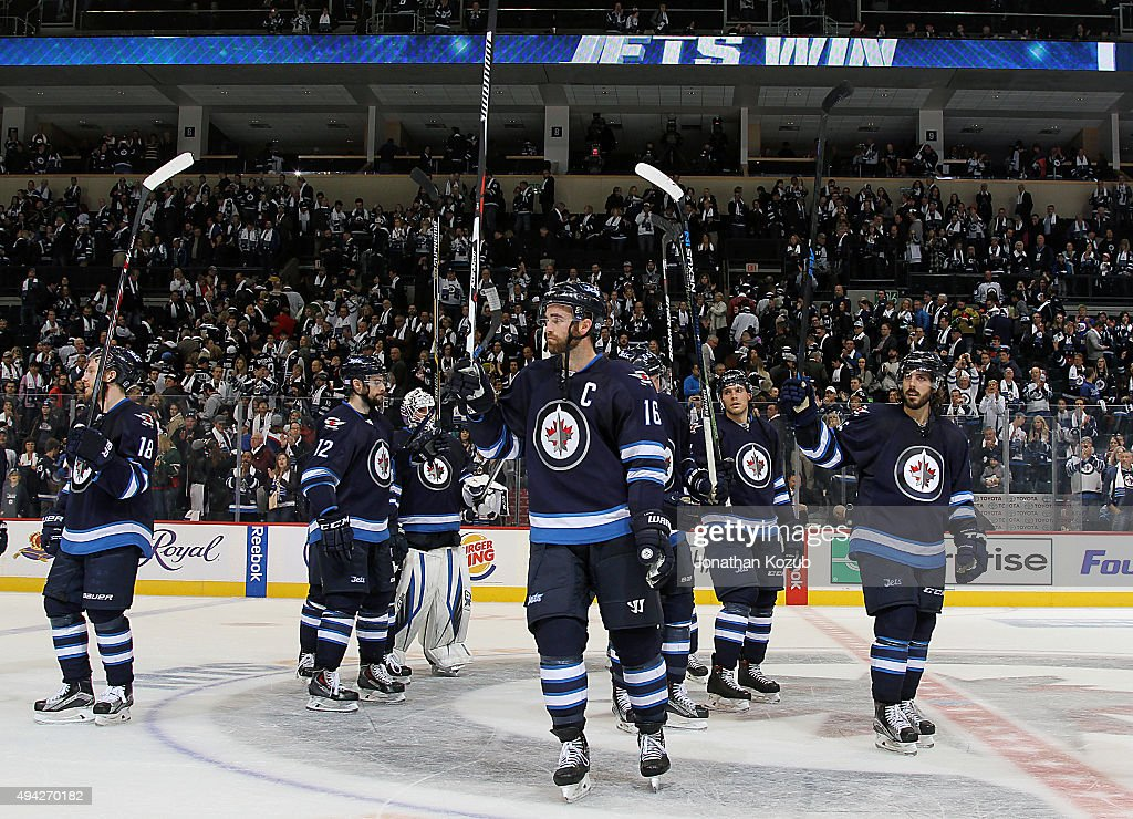 Andrew Ladd #16 of the Winnipeg Jets and teammates salute the fans as they celebrate a 5-4 victory over the Minnesota Wild at the MTS Centre on October 25, 2015 in Winnipeg, Manitoba, Canada.