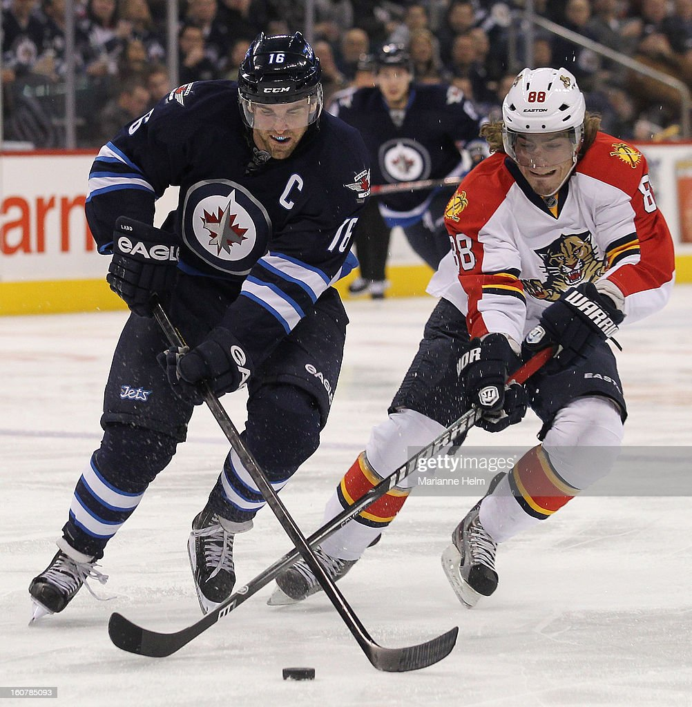Andrew Ladd #16 of the Winnipeg Jets battles with Peter Mueller #88 of the Florida Panthers during second period action on February 5, 2013 at the MTS Centre in Winnipeg, Manitoba, Canada.