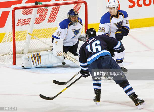 Andrew Ladd of the Winnipeg Jets gets a shot on goaltender Jaroslav Halak of the St Louis Blues as defenseman Kevin Shattenkirk of the Blues watches...