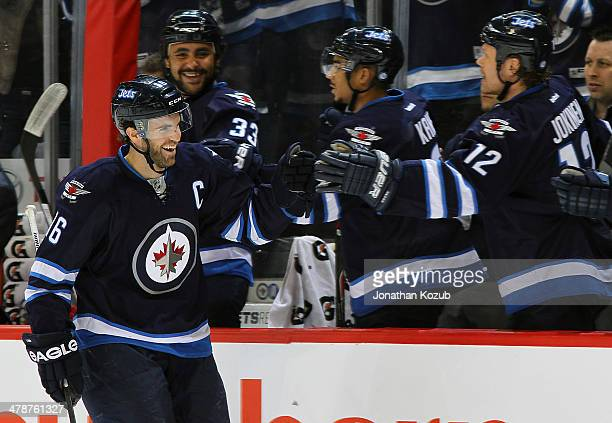Andrew Ladd of the Winnipeg Jets gets congratulated at the bench after scoring a first period goal against the New York Rangers at the MTS Centre on...