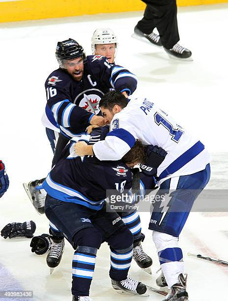 Andrew Ladd of the Winnipeg Jets jumps in to help teammate Bryan Little as he gets into a scrum with Cedric Paquette of the Tampa Bay Lightning...