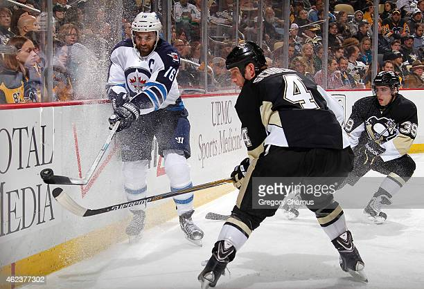 Andrew Ladd of the Winnipeg Jets moves the puck in front of Rob Scuderi of the Pittsburgh Penguins at Consol Energy Center on January 27 2015 in...