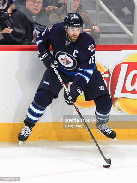 Andrew Ladd of the Winnipeg Jets plays the puck along the boards during secondperiod action against the Colorado Avalanche at the MTS Centre on...
