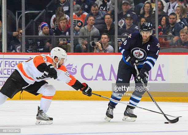 Andrew Ladd of the Winnipeg Jets plays the puck as Sam Gagner of the Philadelphia Flyers defends during thirdperiod action at the MTS Centre on...