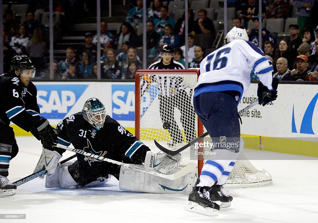 Andrew Ladd #16 of the Winnipeg Jets scores a goal past Antti Niemi #31 and Joe Pavelski #8 of the San Jose Sharks at SAP Center on March 27, 2014 in San Jose, California.