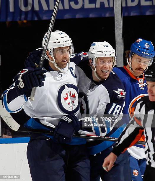 Andrew Ladd of the Winnipeg Jets scores at 14:39 of the second period against the New York Islanders and is joined by Bryan Little at the Nassau...
