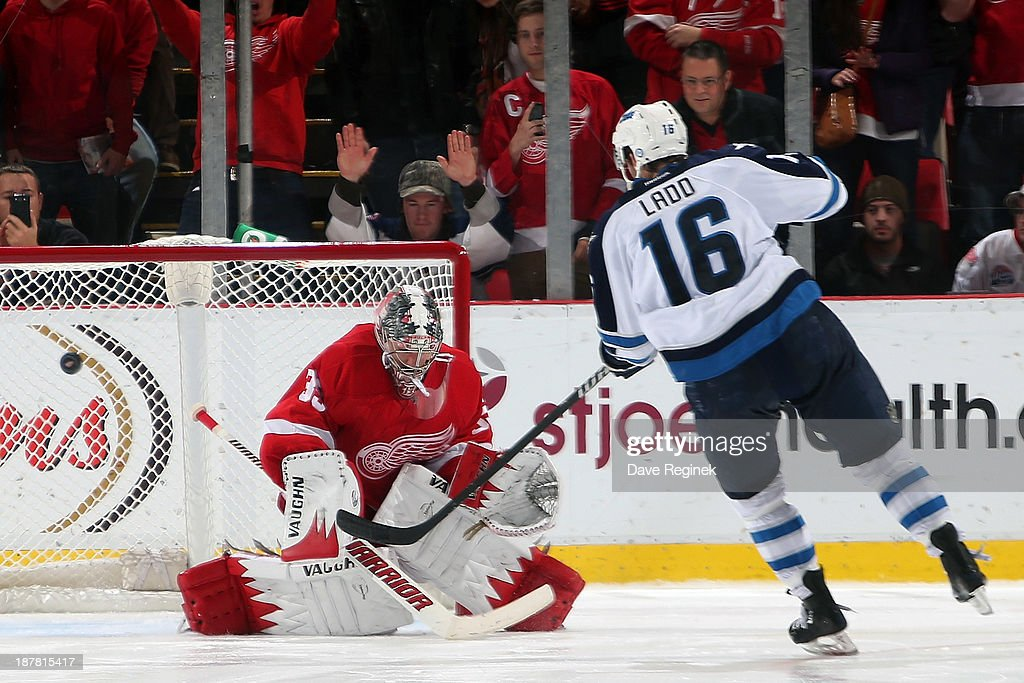 Andrew Ladd #16 of the Winnipeg Jets scores the game winner on Jimmy Howard #35 of the Detroit Red Wings in a shootout during an NHL game at Joe Louis Arena on November 12, 2013 in Detroit, Michigan. The Winnipeg Jets defeated the Detroit Red Wings 3-2 in a shootout