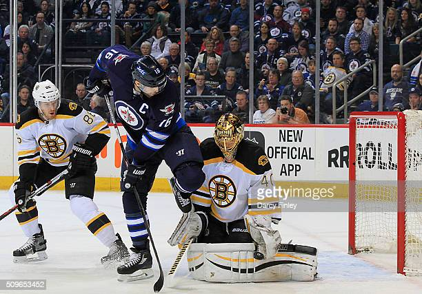 Andrew Ladd of the Winnipeg Jets watches as goaltender Tuukka Rask of the Boston Bruins makes a glove save during first period action at the MTS...