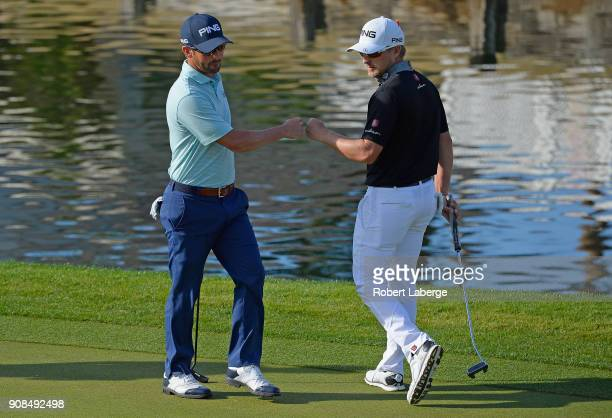 Andrew Landry and Austin Cook react after Landry made his birdie putt on the 13th hole during the final round of the CareerBuilder Challenge at the...