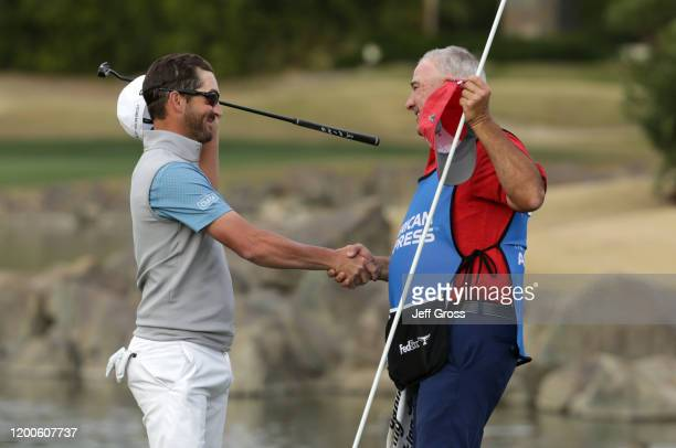 Andrew Landry celebrates with his caddie Terry Walker after putting in to win on the 18th green during the final round of The American Express...