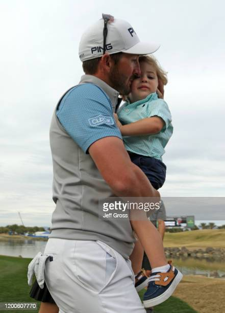 Andrew Landry celebrates with his wife Elizabeth and son Brooks after putting in to win on the 18th green during the final round of The American...