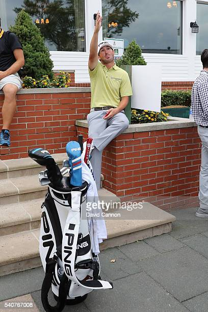 Andrew Landry of the United States sits near the clubhouse after play was suspended by dangerous weather during the first round of the US Open at...