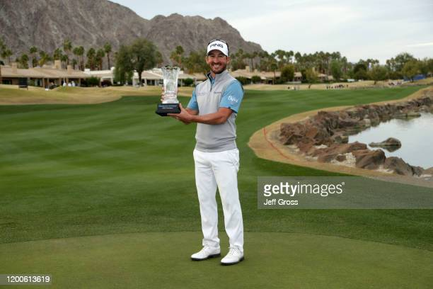 Andrew Landry poses with the trophy on the 18th green during the final round of The American Express tournament at the Stadium Course at PGA West on...