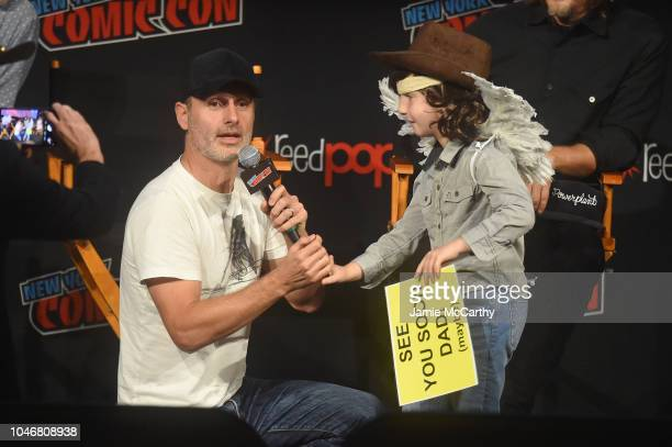 Andrew Lincoln speaks to a cosplayer dressed as Carl Grimes onstage during the NYCC panel and fan screening of 'The Walking Dead' episode 901 at The...