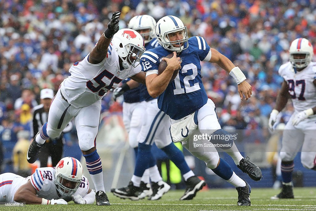 Andrew Luck #12 of the Indianapolis Colts is chased down by Jerry Hughes #55 of the Buffalo Bills during the second half at Ralph Wilson Stadium on September 13, 2015 in Orchard Park, New York.