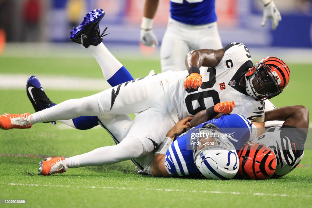 Andrew Luck #12 of the Indianapolis Colts is taken down by Darius Phillips #38 and Michael Johnson #90 of the Cincinnati Bengals at Lucas Oil Stadium on September 9, 2018 in Indianapolis, Indiana.