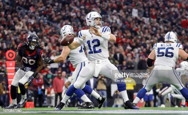 Andrew Luck of the Indianapolis Colts looks to pass under pressure by Jadeveon Clowney of the Houston Texans in the fourth quarter at NRG Stadium on...
