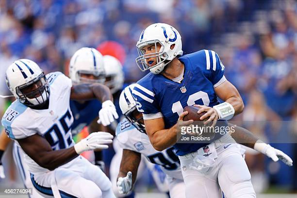 Andrew Luck of the Indianapolis Colts looks to throw a pass while under pressure from Jurrell Casey and Kamerion Wimbley of the Tennessee Titans in...