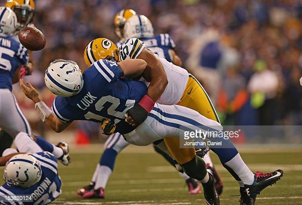 Andrew Luck of the Indianapolis Colts looses the ball as he is hit by Nick Perry of the Green Bay Packers at Lucas Oil Stadium on October 7, 2012 in...