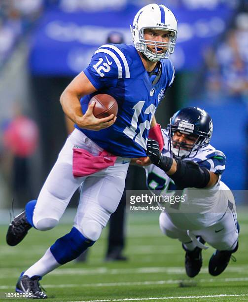 Andrew Luck of the Indianapolis Colts runs the ball as Jordan Hill of the Seattle Seahawks tries to tackle from behind at Lucas Oil Stadium on...