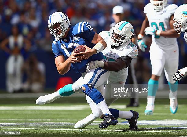 Andrew Luck of the Indianapolis Colts runs with the ball while being tackled by Dannell Ellerbe of the Miami Dolphins during the Dolphins 2420 win at...