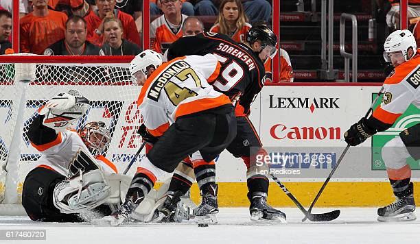 Andrew MacDonald and Shayne Gostisbehere of the Philadelphia Flyers battle for the puck in front of goaltender Steve Mason against Nick Sorensen of...