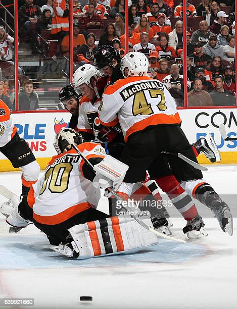 Andrew MacDonald Nick Cousins and Michal Neuvirth of the Philadelphia Flyers clear the puck from their crease against Kyle Palmieri and Sergey...