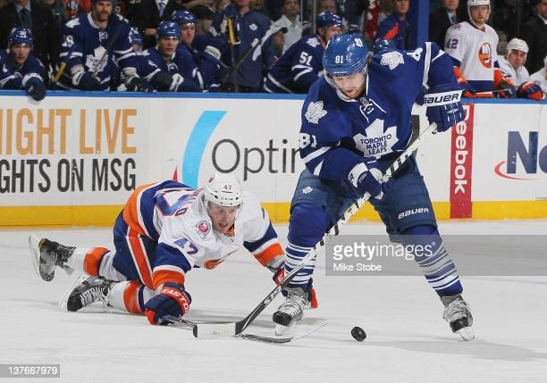 Andrew MacDonald of the New York Islanders attemps to steal the puck from Phil Kessel of the Toronto Maple Leafs at Nassau Veterans Memorial Coliseum...