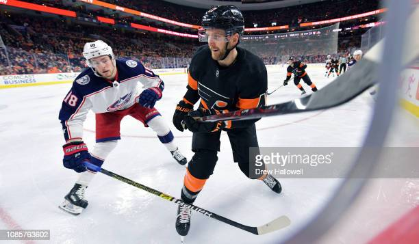 Andrew MacDonald of the Philadelphia Flyers and Pierre-Luc Dubois of the Columbus Blue Jackets skate for position at Wells Fargo Center on December...