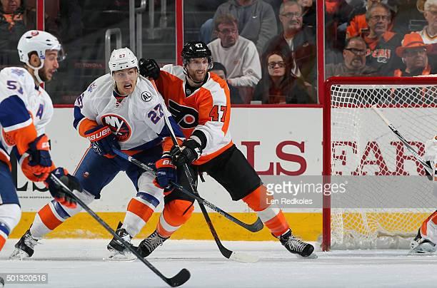 Andrew MacDonald of the Philadelphia Flyers battles alongside the net against Anders Lee of the New York Islanders on December 8 2015 at the Wells...