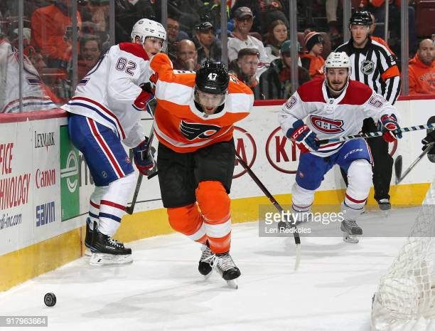 Andrew MacDonald of the Philadelphia Flyers battles for the loose puck against Artturi Lehkonen and Victor Mete of the Montreal Canadiens on February...