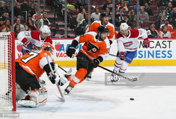 Andrew MacDonald of the Philadelphia Flyers clears the puck out of the crease of goaltender Brian Elliott against Alex Galchenyuk and Jonathan Drouin...
