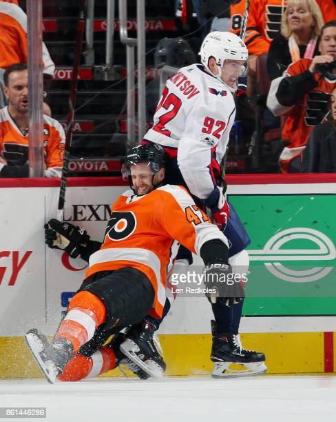 Andrew MacDonald of the Philadelphia Flyers falls to the ice after a check by Evgeny Kuznetsov of the Washington Capitals on October 14 2017 at the...