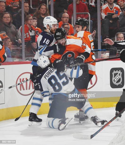 Andrew MacDonald of the Philadelphia Flyers goes up against Bryan Little and Mathieu Perreault of the Winnipeg Jets during the third period at the...