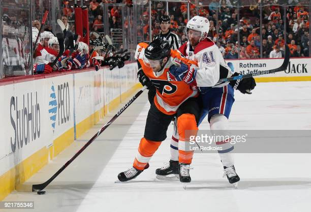 Andrew MacDonald of the Philadelphia Flyers keeps possession of the puck along the boards while battling with Paul Byron of the Montreal Canadiens on...