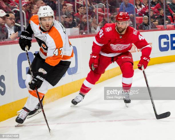 Andrew MacDonald of the Philadelphia Flyers passes the puck in front of Luke Glendening of the Detroit Red Wings during an NHL game at Little Caesars...