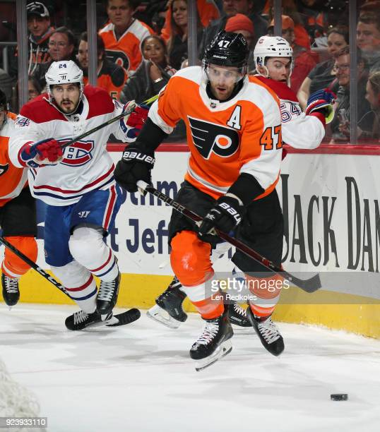 Andrew MacDonald of the Philadelphia Flyers skates the puck against Phillip Danault and Charles Hudon of the Montreal Canadiens on February 20 2018...