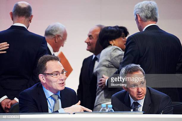 Andrew Mackenzie chief executive officer of BHP Billiton Ltd front left and Graham Kerr chief financial officer front right speak to attendees as...