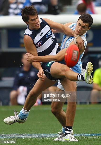 Andrew Mackie of the Cats kicks whilst being tackled by Scott Thompson of the Kangaroos during the round seven AFL match between the Geelong Cats and...