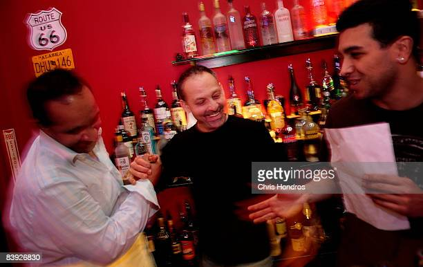 Andrew MacLerio is congratulated by fellow New York Bartending School students after passing his final exam December 5 2008 in New York City...