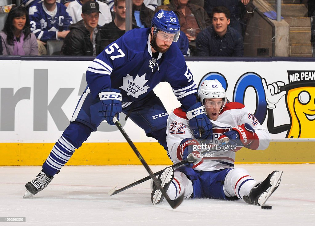 Andrew MacWilliam #57 of the Toronto Maple Leafs battles for the puck with Dale Weise #22 of the Montreal Canadiens during NHL game action April 11, 2015 at the Air Canada Centre in Toronto, Ontario, Canada.