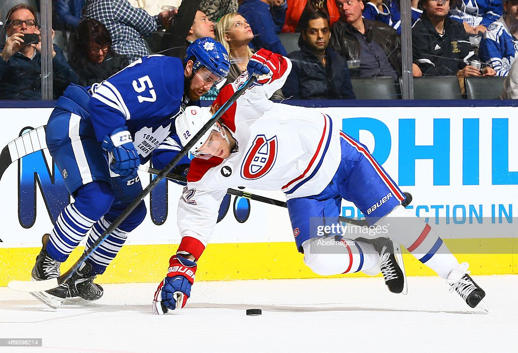 Andrew MacWilliam #57 of the Toronto Maple Leafs knocks down Dale Weise #22 of the Montreal Canadiens during NHL action at the Air Canada Centre April 11, 2015 in Toronto, Ontario, Canada.