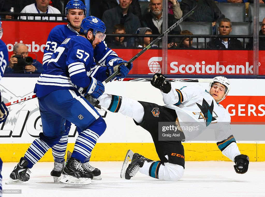 Andrew MacWilliam #57 of the Toronto Maple Leafs knocks down Mirco Mueller #41 of the San Jose Sharks during game action on March 19, 2015 at Air Canada Centre in Toronto, Ontario, Canada.