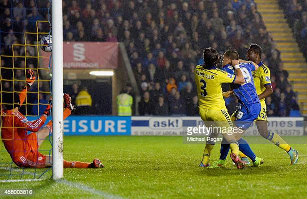 Andrew Mangan of Shrewsbury Town tussles with Filipe Luis of Chelsea as he scores their first goal past Petr Cech of Chelsea during the Capital One...